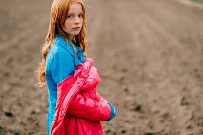 Beautiful strange red head girl in long blue coat and pink warm jacket spends a lot of time on the big empty field.