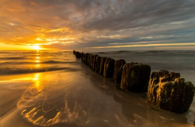Wall mural beautiful sunset on the Baltic Sea, waves washing the old wooden breakwaters