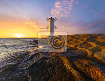 Beautiful sunset over a windmill-shaped lighthouse, Swinoujscie, Poland