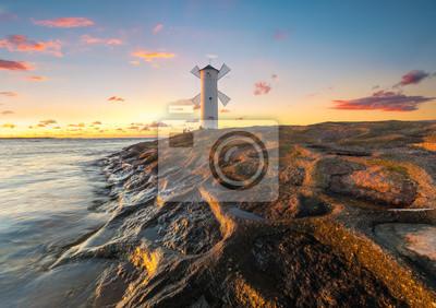 Beautiful sunset over a windmill-shaped lighthouse, Swinoujscie, Poland.