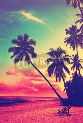 Wall mural Beautiful tropical beach with silhouettes of palm trees at sunset