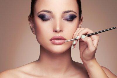 Wall mural Beautiful woman face. beauty girl with Perfect make-up.Makeup artist applies lipstick.cosmetics