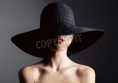 Wall mural Beautiful woman in hat. Retro fashion. Dark Background.