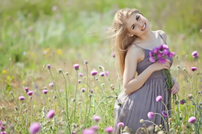 Wall mural Beautiful woman with bunch in a flowers field