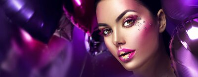 Wall mural Beauty fashion model girl creative art makeup with gems. Woman face over purple, pink and violet air balloons background