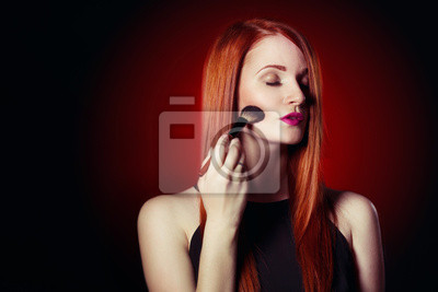 Beauty red head girl with makeup brush. Makeover. Perfect Skin.