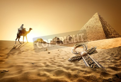 Wall mural Bedouin on camel near pyramids and ankh in desert