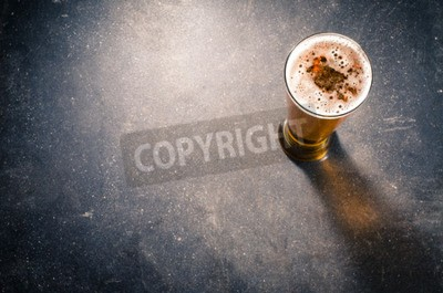 Wall mural Beer glass on dark table