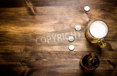 Wall mural Beer style- bottle, beer in the glass and covers on wooden table.