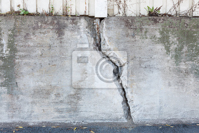Big crack in messy outdoor concrete wall