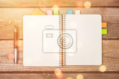 Blank notebook and pen on wooden background