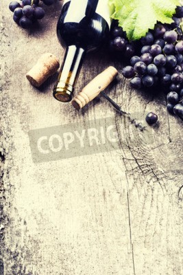 Wall mural Bottle of dark wine, grape and corks on old wooden background
