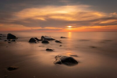 Boulders in the sea in the Wolin National Park in the light of the setting sun, Poland