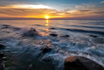 Wall mural Boulders in the sea in the Wolin National Park in the light of the setting sun, Poland