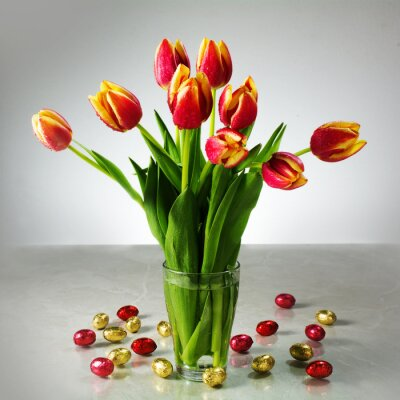 Wall mural bouquet of fresh tulips and small red yellow chocolate easter eg