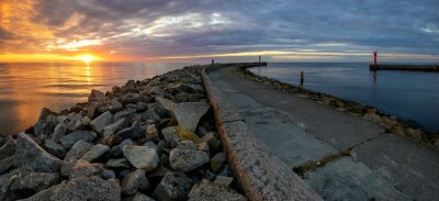 Wall mural breakwater at the entrance to port during sunset
