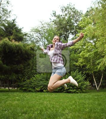 Brunette girl jumping in summer park
