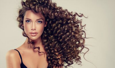 Wall mural Brunette girl with long and shiny curly hair . Beautiful model with wavy hairstyle .