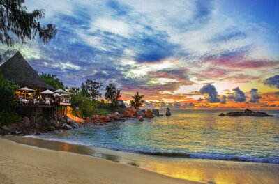 Cafe on tropical beach at sunset