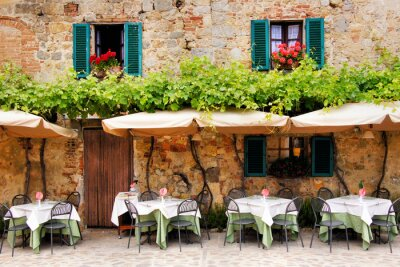 Wall mural Cafe tables and chairs outside a stone building in Tuscany