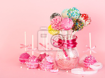 Wall mural Cake pops with pink icing and decoration on paper form and colorful cake pops in glass vase