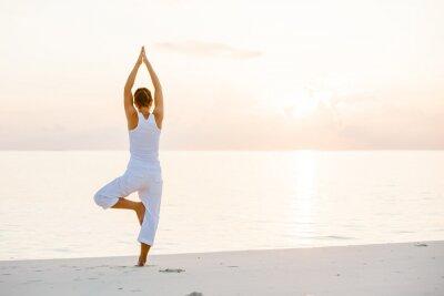 Wall mural Caucasian woman practicing yoga at seashore