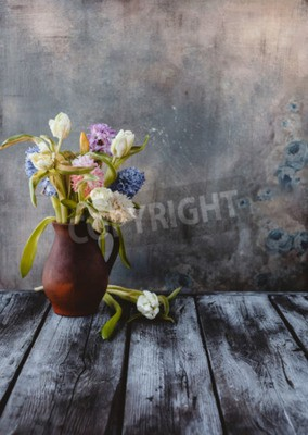 Wall mural Ceramic jug with spring flowers on wooden table