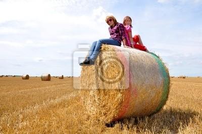 children sitting on a bale of straw