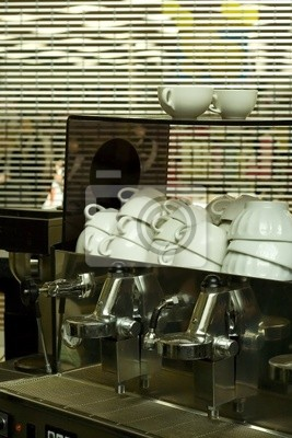 Clean coffee cups and a coffee machine in a closed cafe