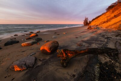Cliffs and sandy beach In Wolin National Park in the light of the setting sun