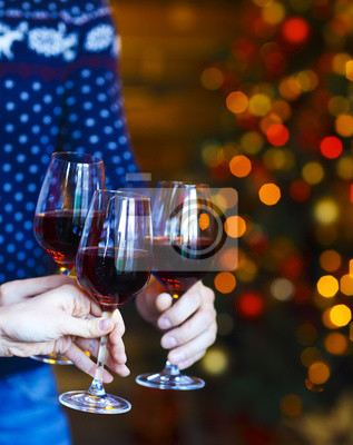 Clinking glasses of red wine in hands on Christmas lights backgr