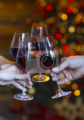 Clinking glasses of wine in hands on bright christmas lights bac
