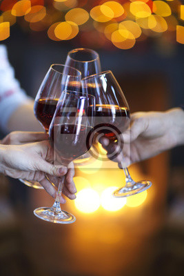 Clinking glasses of wine in hands on bright lights background
