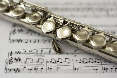 Wall mural Close up flute on flute sheet music background