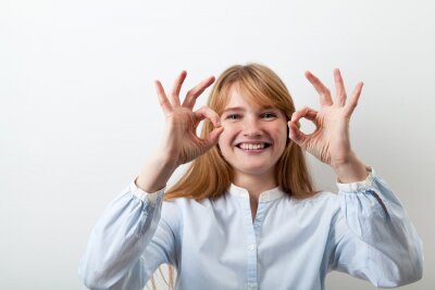 Close-up headshot of red-headed girl with freckles dressed in casual blue shirt showing a sign of approval with her fingers and smiling happily. White background, copy space.