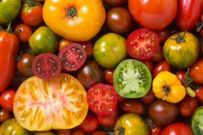 Wall mural Close up of colorful tomatoes, some sliced, shot from above
