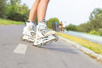Wall mural Close up of girl rollerblading in park. Outdoor, recreation, lifestyle, rollerblading.