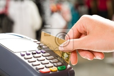 Close-up of hand holding plastic card in payment machine
