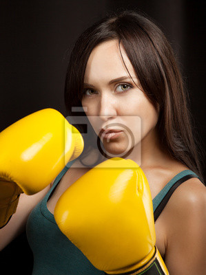 Close up portrait of a girl in yellow boxing gloves