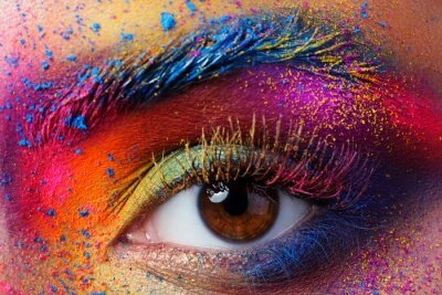 Wall mural Close up view of female eye with bright multicolored fashion mak