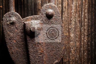 Closeup of a very old rustic padlock on a wooden door.