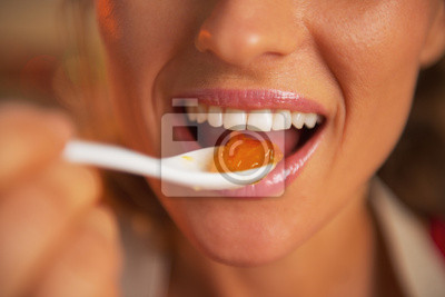 Wall mural Closeup on happy young woman eating orange jam