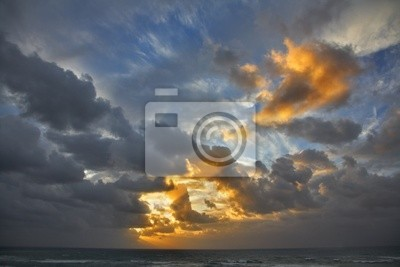 Clouds above the sea the sun shined by beams on a decline