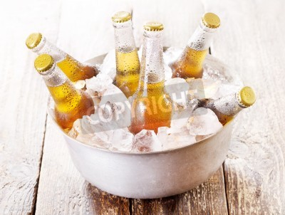 Wall mural cold bottles of beer in bucket with ice on wooden table
