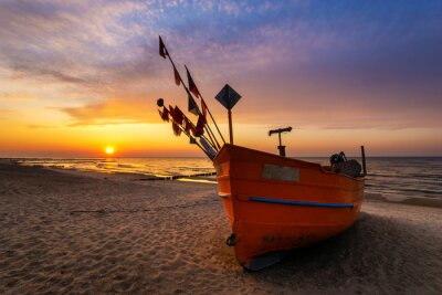 Wall mural Colorful fishing boat on a sandy sea beach during a beautiful sunset