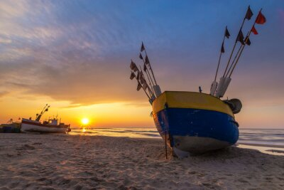 Colorful fishing boat on a sandy sea beach during a beautiful sunset