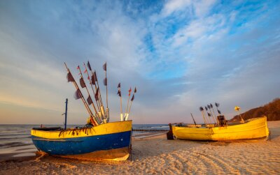 Wall mural Colorful fishing boats on a sandy sea beach during a beautiful sunset