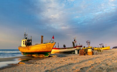 Colorful fishing boats on a sandy sea beach during a beautiful sunset