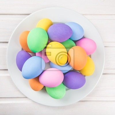Colorful pastel easter eggs on white wooden background
