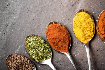 Wall mural Colorful spices on metal spoons on black rough rock surface.